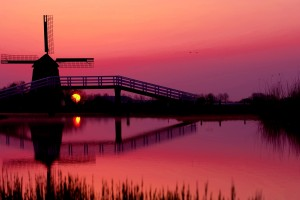 Silhouette of windmill by lake at dusk --- Image by © JILL FLUSEMANN/PPSOP/Corbis