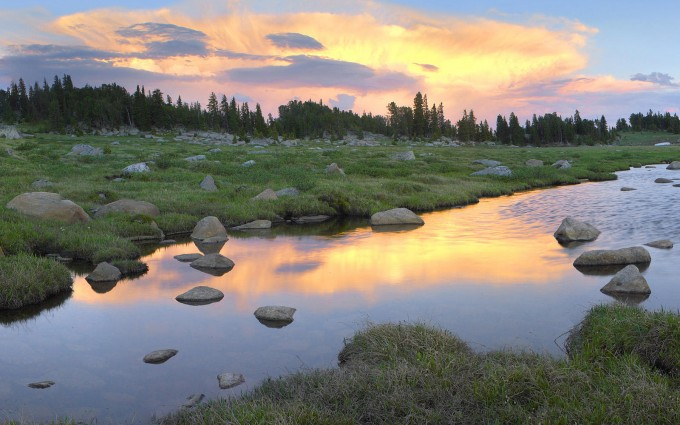 Clouds and sunset reflected in stream, Hellroaring Plateau, Montana