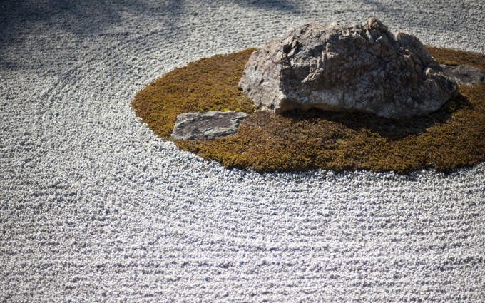 stones, moss and raked gravel in a traditional dry zen rock garden